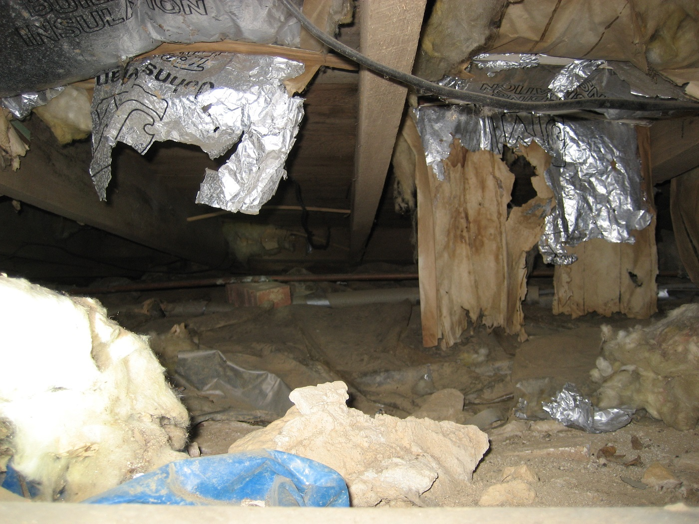 Typical crawlspace with old insulation hanging loose