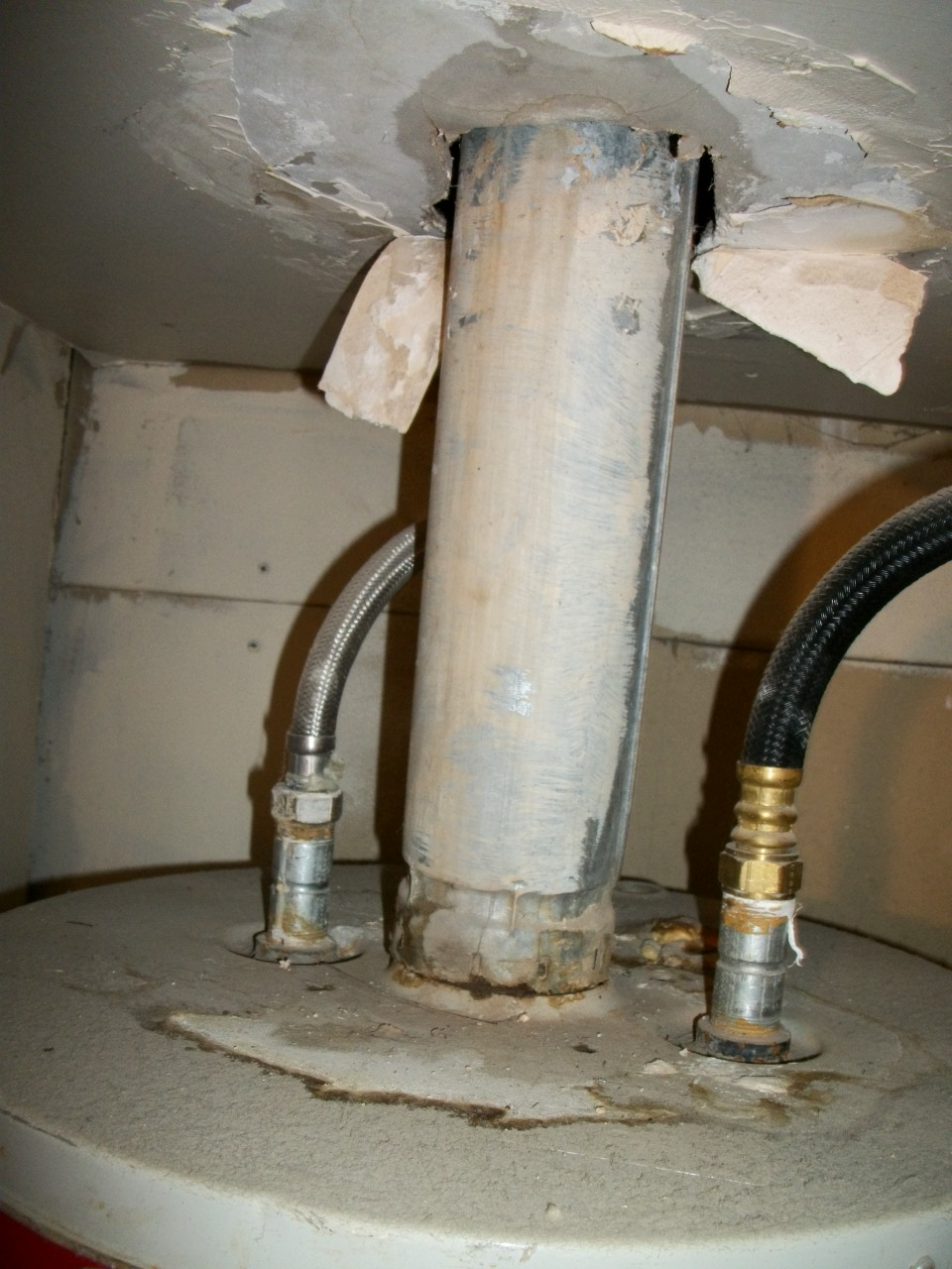 water heater flue should not be attached directly to the water heater. Also, the flue is in contact with the drywall above
